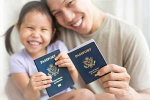 Father and daughter holding passports who have achieved successful cancellation of removal