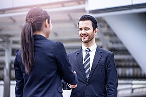 an employee shaking hands with his manager who holds an employment visa