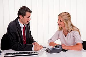 Immigration attorney sitting with client at table