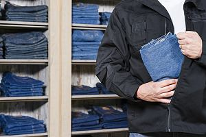 Man shoplifting a pair of jeans