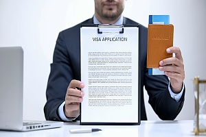 a person who is ready to give a visa interview holding a clipboard and passport