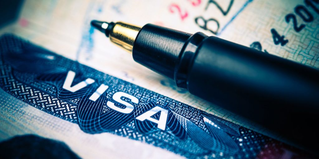 Close up of united States Visa and a pen. EB-4 visa stands for employment based fourth preference