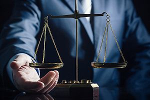 Weight scale of justice and a lawyer in background. You need an attorney to complete your EB-4 application