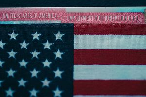 Employment authorization card under flag of USA