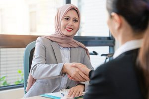 A foreign EB-3 visa applicant shaking hands with an official after reviewing her requirements