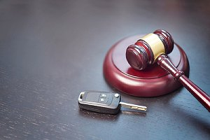 Car key and gavel, a traffic violation concept. Driving without a license is a misdemeanor Class 2