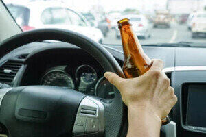 Man Driving with Liquor Bottle in Hand