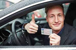 Man in a car holding driver's license. Driving without a license may seem self-explanatory