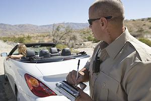 Police officer writing traffic ticket to a woman for driving without a valid license