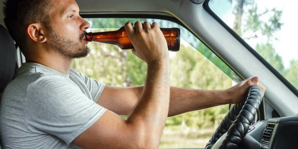 man holds alcohol in his hand while driving violates traffic rule