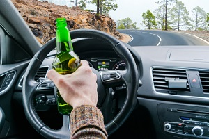 young man driving a car on the road with a bottle of beer