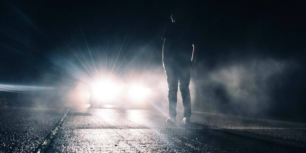 person standing on the road and car coming in speed