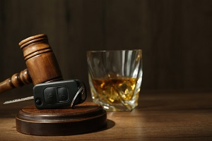 car key gavel near glass of alcohol on wooden table needing to removing dui from record