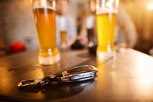 car keys on the bar table in front of glasses with draft beer