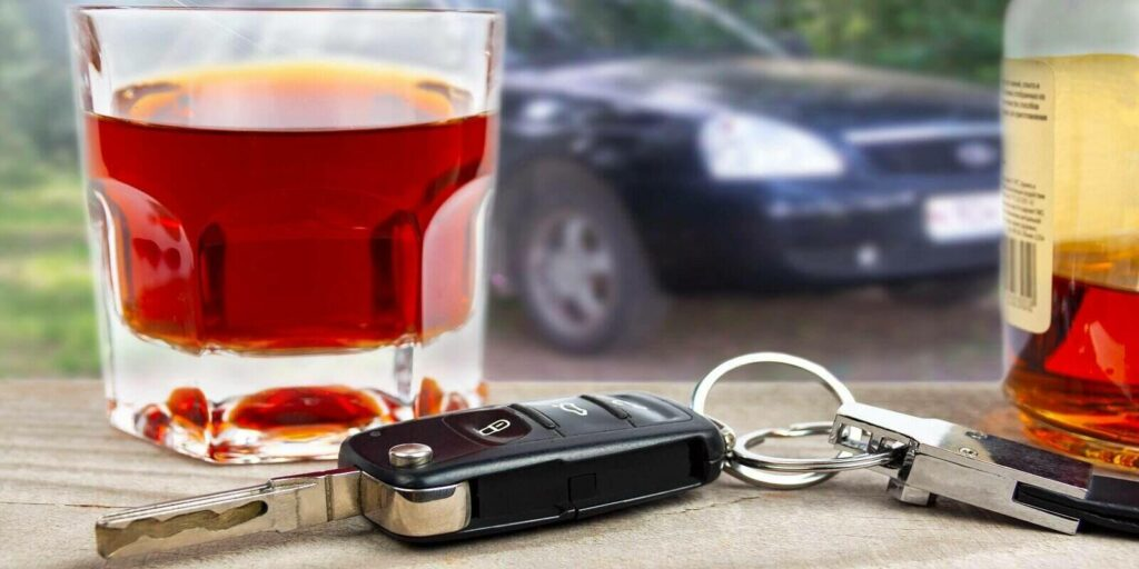 car keys with a glass of liquor on the background of the car