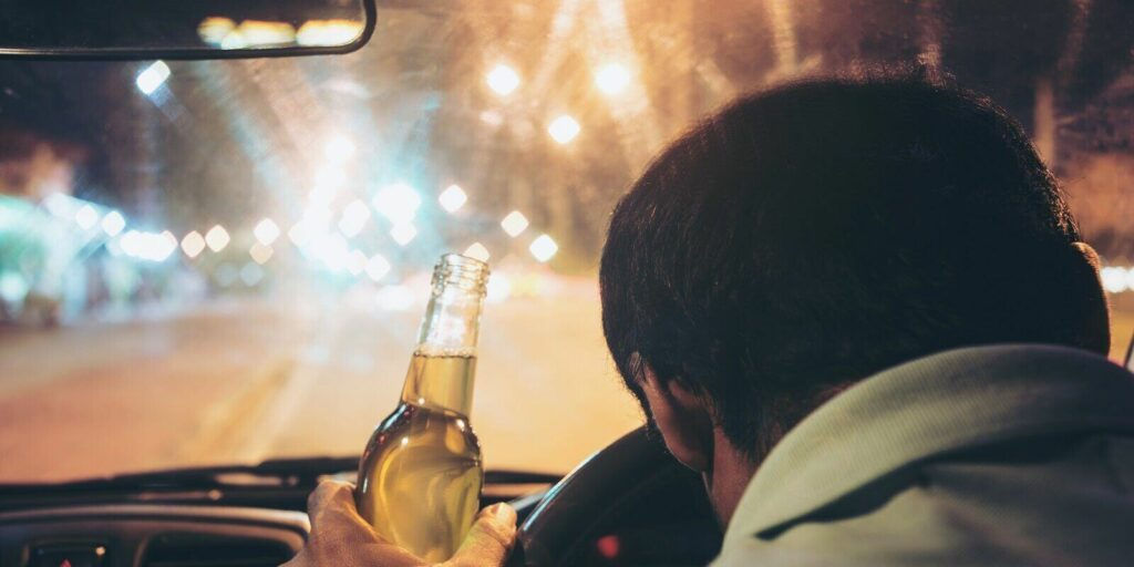 drunk young man drives a car with a bottle of beer