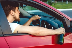drunk young man driving a car with a bottle of beer now wondering how long does a dwi stay on your record?