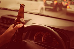 man drink beer while driving car