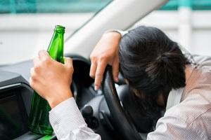 man sleeping in the car with bottle of beer in hand before getting a Aggravated DWI