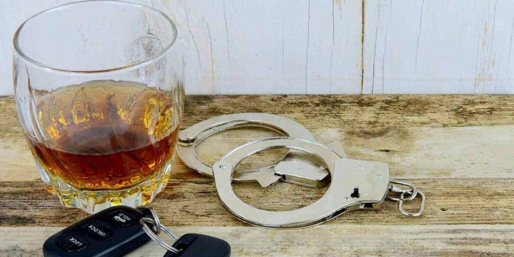 whiskey in a glass on w wooden table with handcuffs and car keys