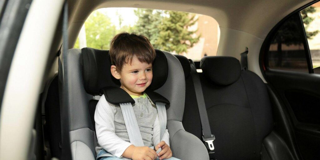 child sitting in safety seat inside car