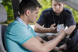 shot of a young driver showing his driving licence to the traffic policeman