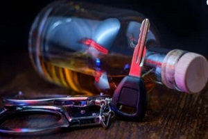 car key handcuffs and alcohol bottle on the table needing VASAP