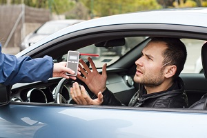 driver arguing with a police officer during test for alcohol content with breathalyzer