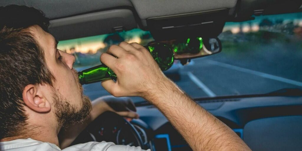 man driving a car with a bottle of beer