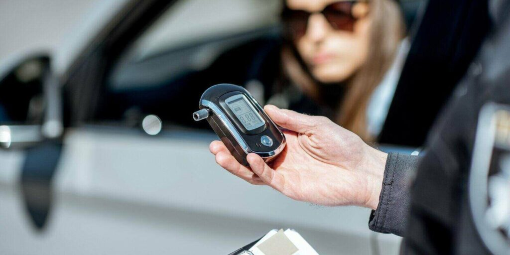 policeman holding device for checking alcohol intoxication while standing near the stopped car with woman driver